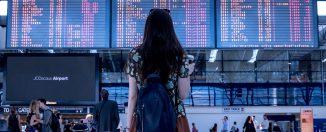 fille devant tableaux destinations aéroport