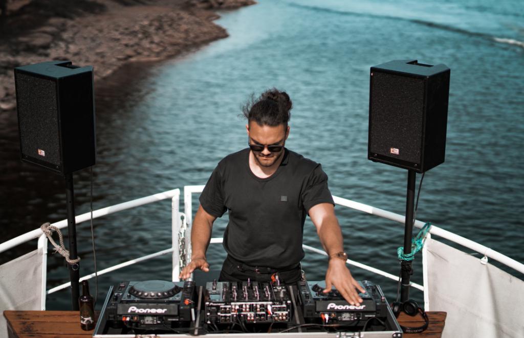 DJ derrière les platines sur la proue d'un bateau