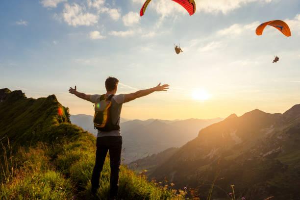 Jeune homme au bord d'une montagne en train de regarder des personnes faire du parapente