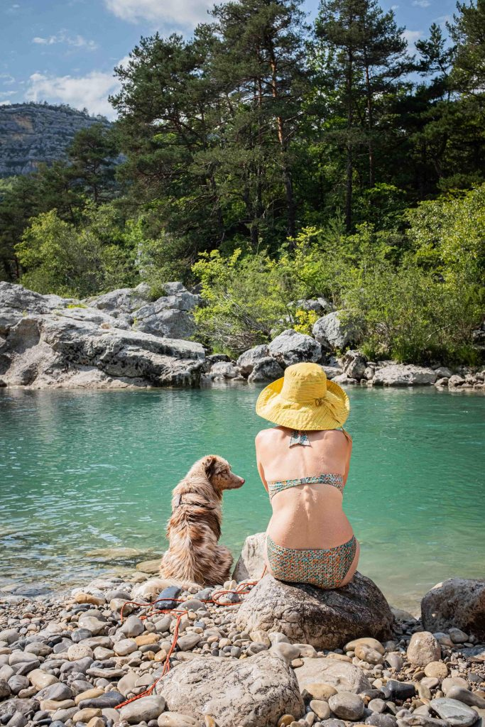 Une femme au bord d'une rivière avec un chien
